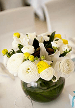 Close up of the Ranunculus, lily, yellow and white table arrangements.