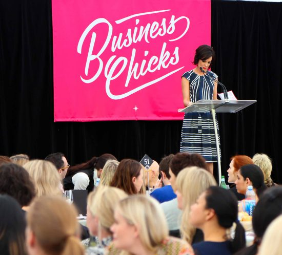 MC Natarsha Belling on stage with our flowers at Business Chicks Lunch with Seth Godin